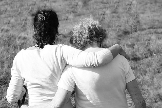 黒い髪の人と金髪の人が肩を組む白黒写真