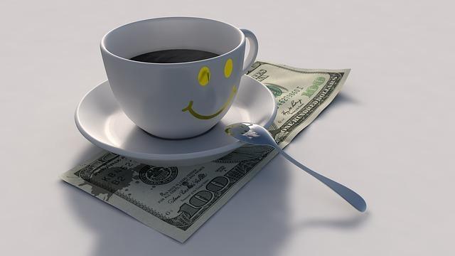ドル札の上にスマイルマークのコーヒーソーサーが乗っている写真