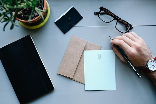 手紙を書こうとする男性の右手とデスクの上の手帳やメガネなど