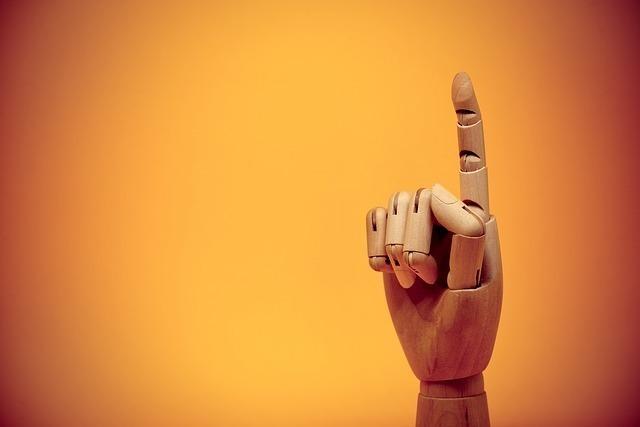 マネキンがオレンジの背景の中で人差し指を上に向けている
