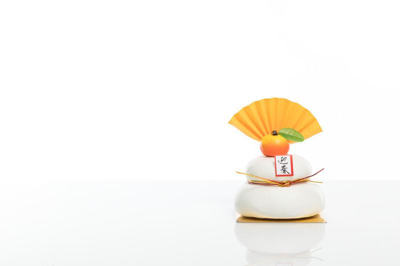 白い背景に橙とセンスがのった二段鏡餅の写真