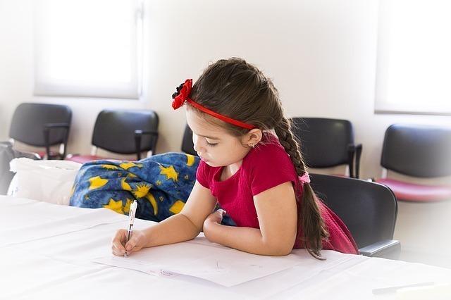 紙にメッセージを書く女の子の画像