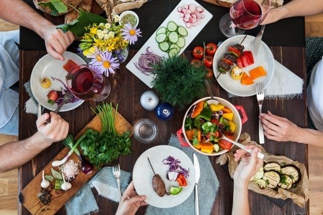 鮮やかな彩の野菜を食べる家族の食事風景