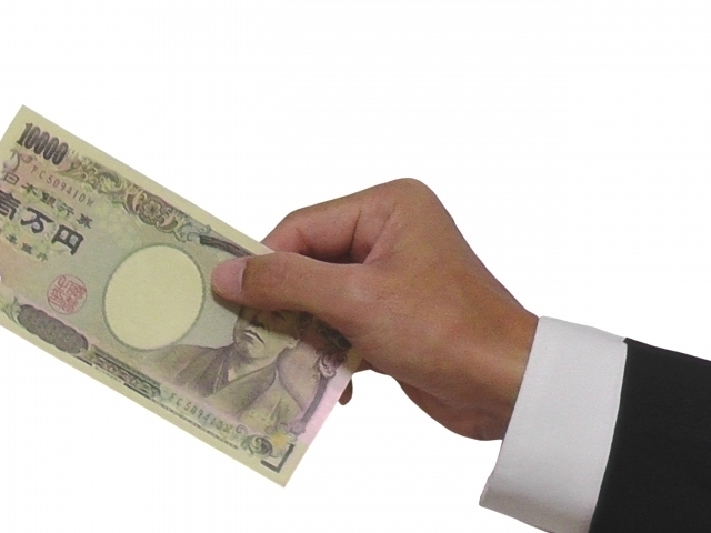 一万円札を持つ男性の手