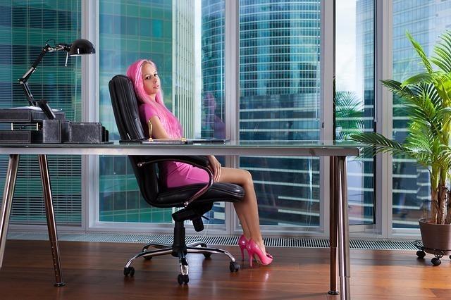 ピンクの服を身にまとい自分専用オフィスで振り向く女性