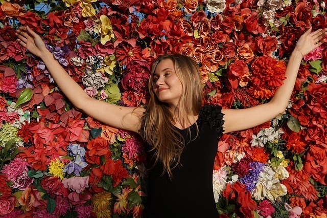 たくさんの花に囲まれ夢見心地の女性