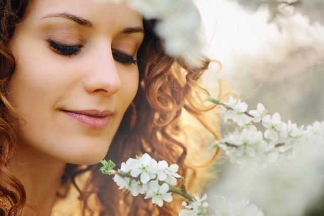 小さな白い花を見つめる女性