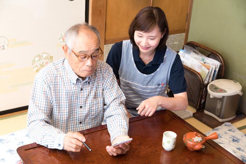 お年寄りにスマホの使い方を教える女性