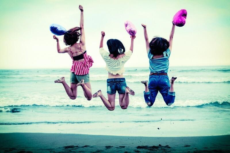 海岸で飛び跳ねる女性3人