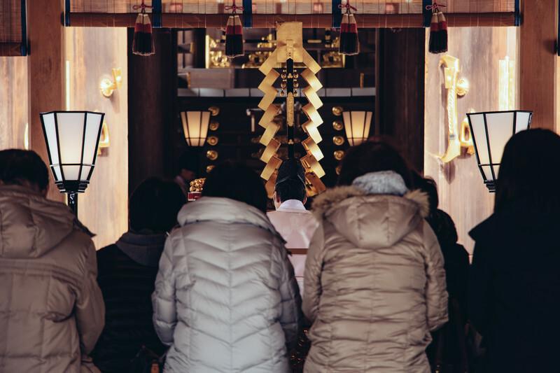 神社でお祓いする人々