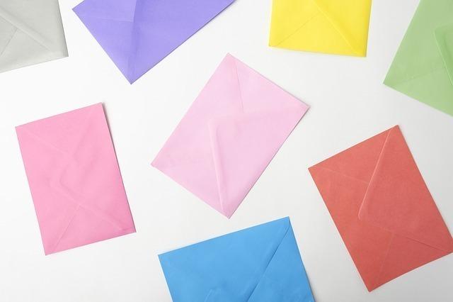 いろいろな色の封筒が広げられている