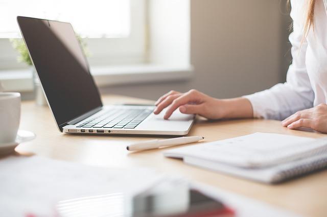ノートパソコンで仕事をする人物の画像
