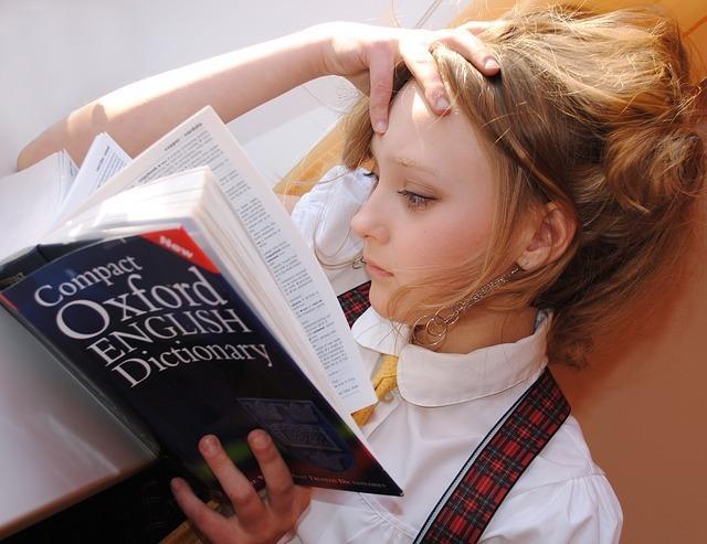 英語辞書を読みながら考え事をしている女性