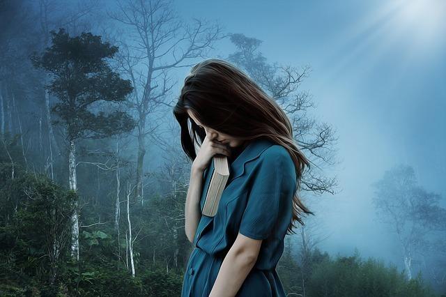 霧の中悩みうつむく女性