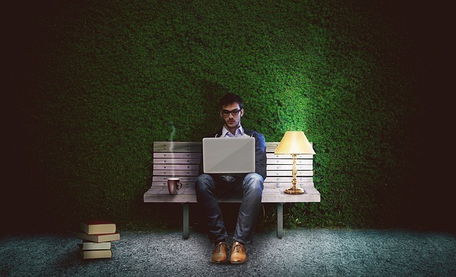 ベンチに座りノートPCで孤独に作業する男性