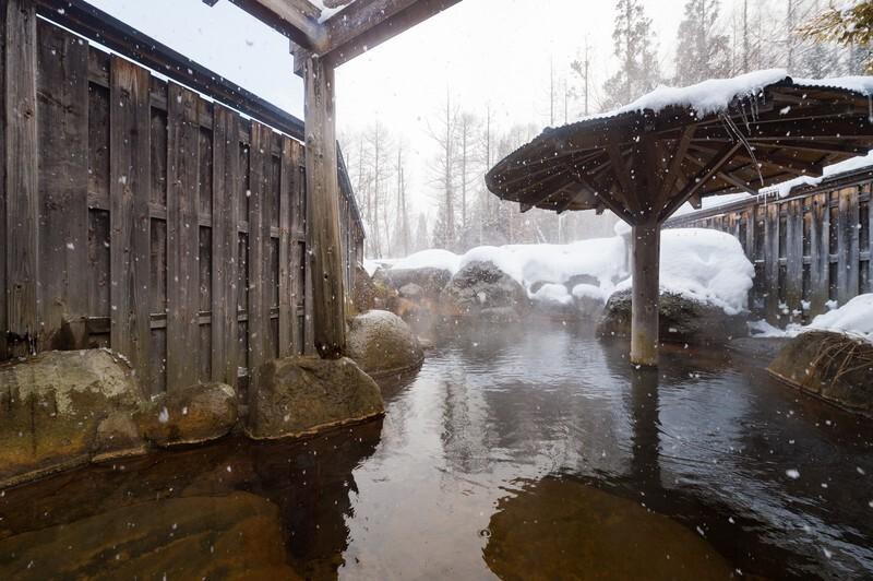 雪の積もった傘屋根のある温泉
