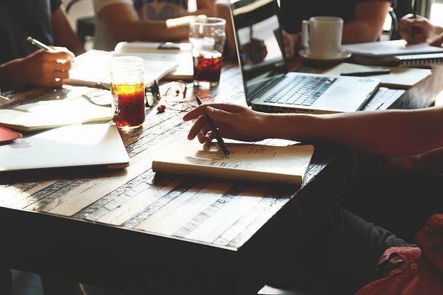 乱雑に仕事道具が置かれたテーブルと案を考える女性の手