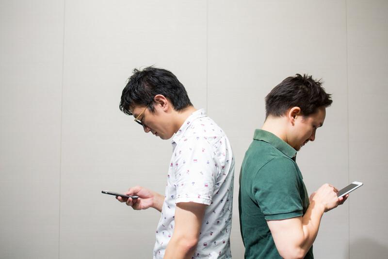 スマートフォンに夢中で相手が見えていない男性2人の画像