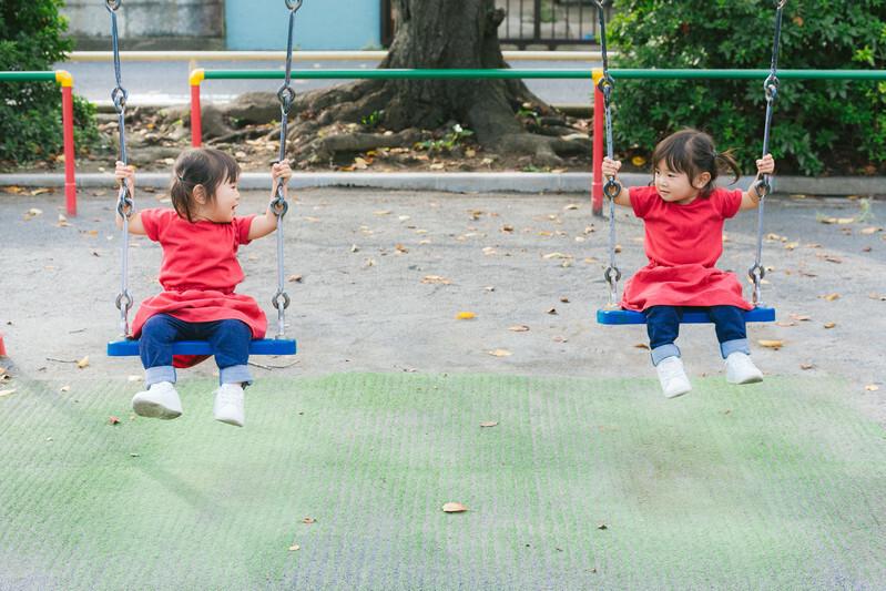 双子の女の子が公園のブランコに乗っている画像
