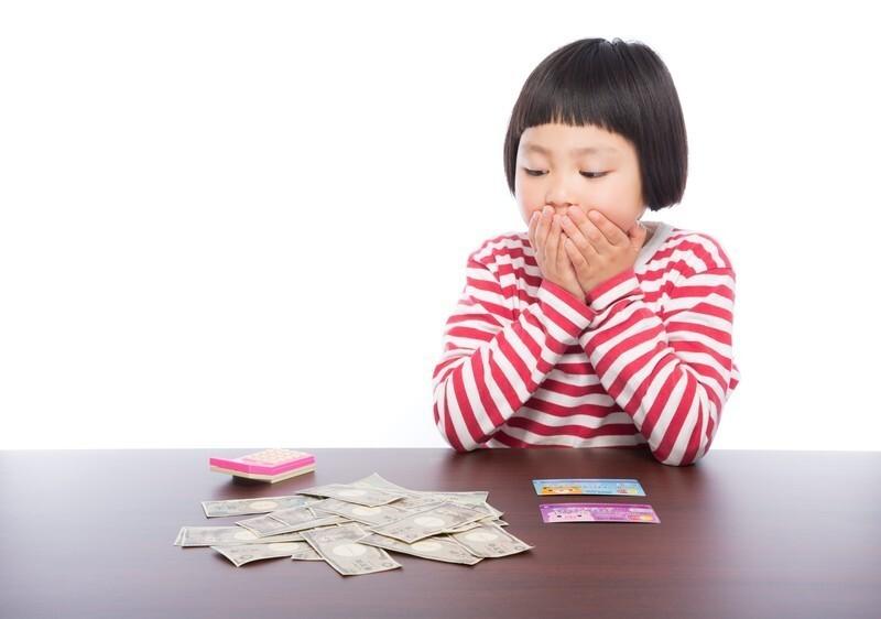 女の子がお金を計算して思ったより多くて驚いてる画像
