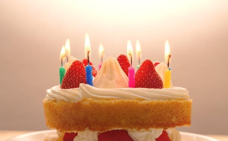 イチゴのケーキの上で火のついた8本のロウソクがたっている画像