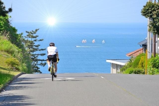自転車に乗った男性が湖に向かって坂を下り始めた画像