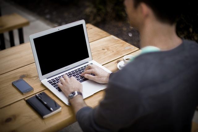 カフェで一人パソコンに向かう男性の画像