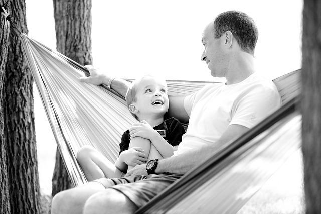 ハンモックに腰かけて見つめ合う親子の画像