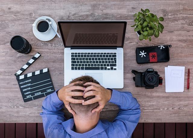 パソコンの前で頭を抱える男性の画像