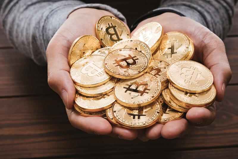 ビットコイン金貨を大量に手にする画像
