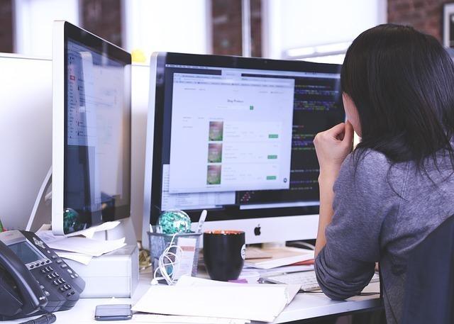 デュアル画面に向かう仕事中の女性の後ろ姿の画像