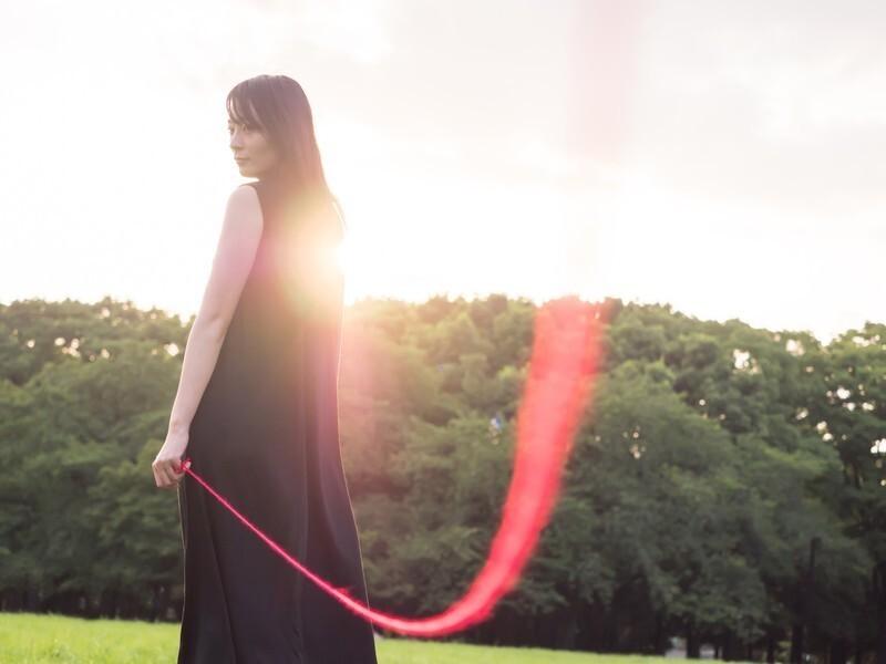 黒いワンピースの女性の赤い糸は遠く遅い恋愛を暗示す画像