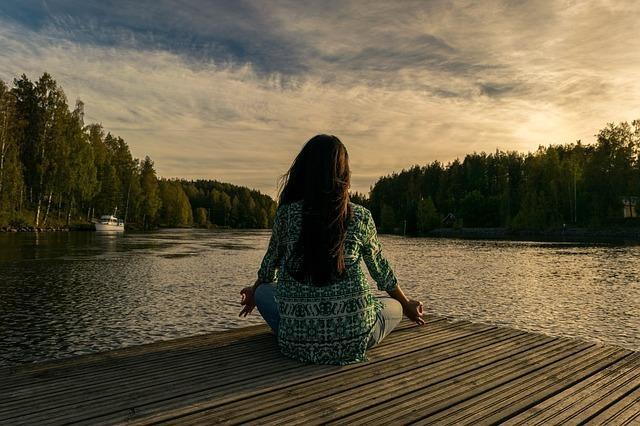 森と湖の前で心静かに瞑想する女性