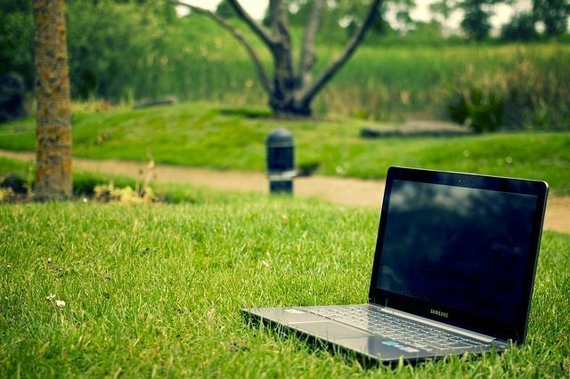 公園でPCを開き自由な環境を象徴する画像