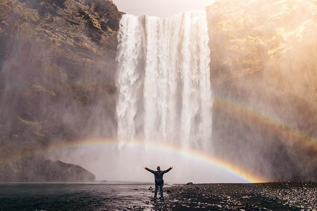 大きな滝の前で両手を広げ、虹がかかっている画像