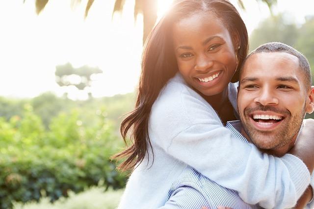 男性の背中におぶさる女性、笑顔のカップルの画像