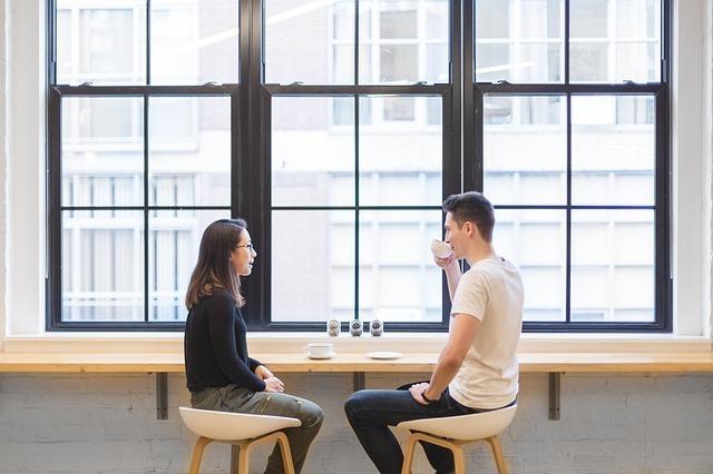 カウンターでコーヒーを飲みながら話す男女