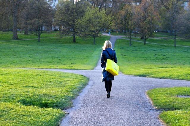 芝生に砂利をしいてできた道を歩く女性の後ろ姿