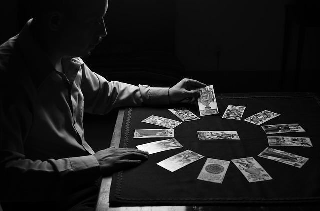 タロットカードで占いをしている男性のモノクロ画像