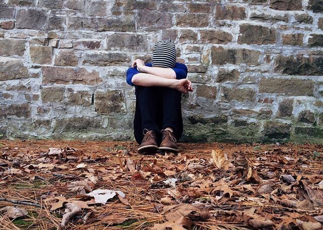 膝を抱え孤独にうつむく男性