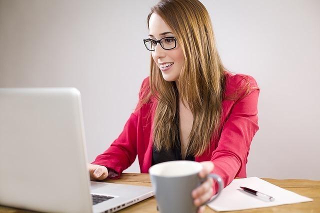眼鏡をかけた女性がマグカップを片手にパソコンを見ている