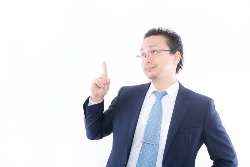 スーツを着た男性がひとさし指を立てて斜め上を見ている