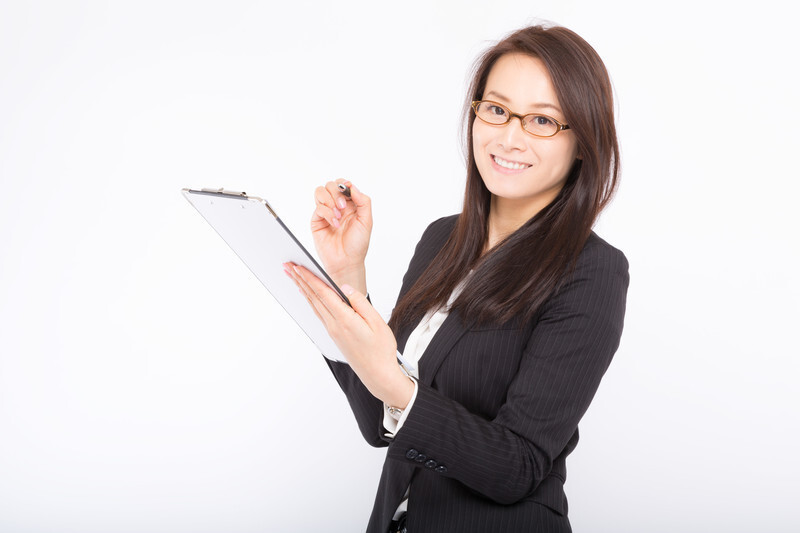 眼鏡をかけたスーツ姿の女性がバインダーとペンを持っている