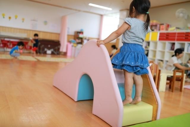 保育園のすべり台に乗ろうとしている女の子の画像