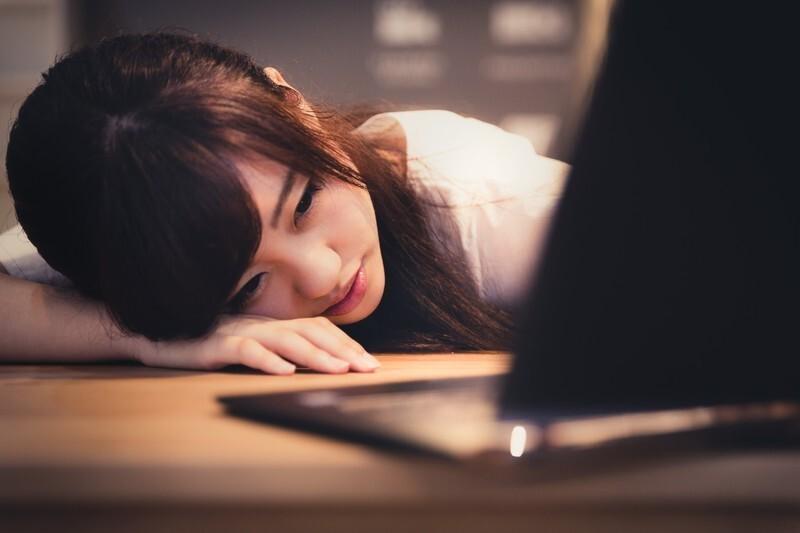 ノートパソコンの前でうつぶせる女性