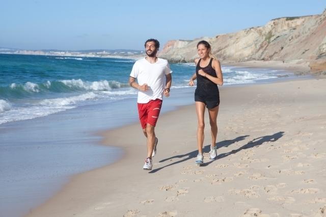 海辺をランニングするカップル