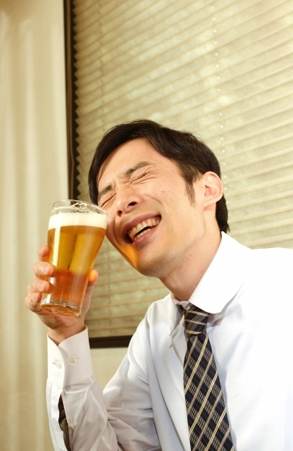 サラリーマンがビールを飲んでいる画像