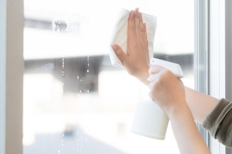 洗剤を使って窓の拭き掃除をしている画像