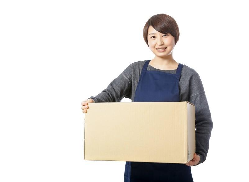 段ボールの荷物を笑顔で運んでいる女性