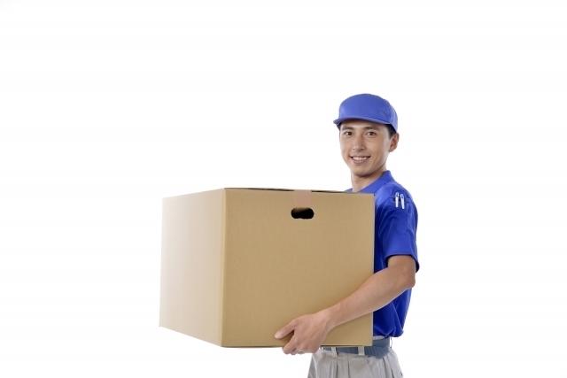 段ボールの荷物を運ぶ宅急便スタッフ